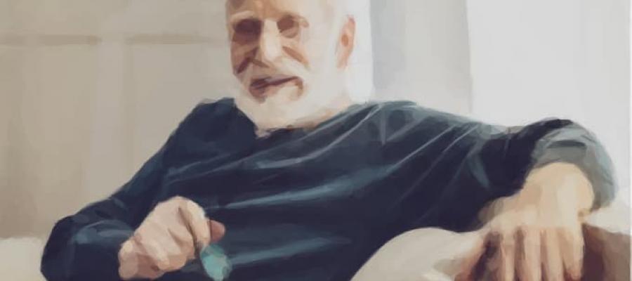 Señor mayor apoyado en su sofá y con las gafas en la mano