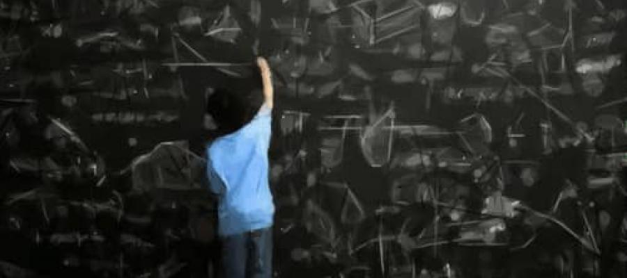 Persona calculando en una pizarra